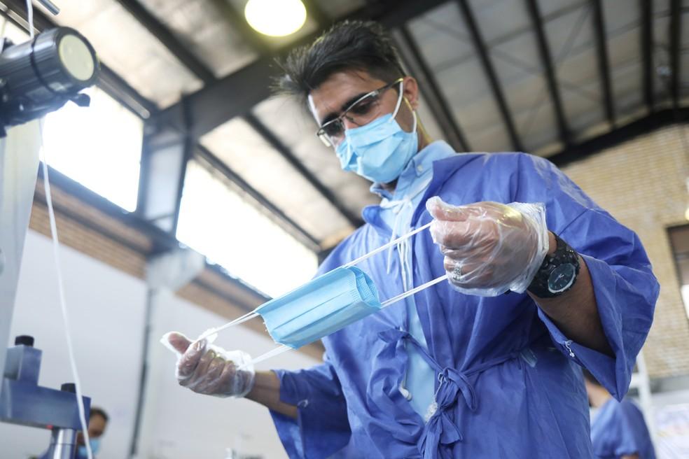 Um funcionário testa uma máscara em uma linha de produção que fabrica máscaras faciais em uma fábrica em Karaj, no Irã, em 28 de junho  — Foto: WANA via Reuters