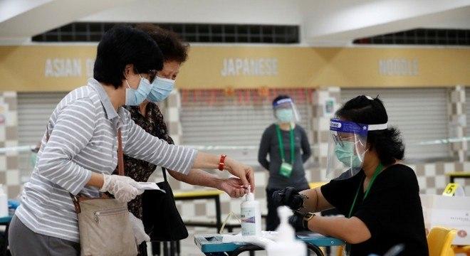 Com máscaras e luvas, Cingapura vota sob onda do coronavírus